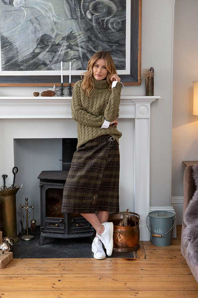 Woman leaning on fireplace wearing cosy knitted jumper and plaid skirt