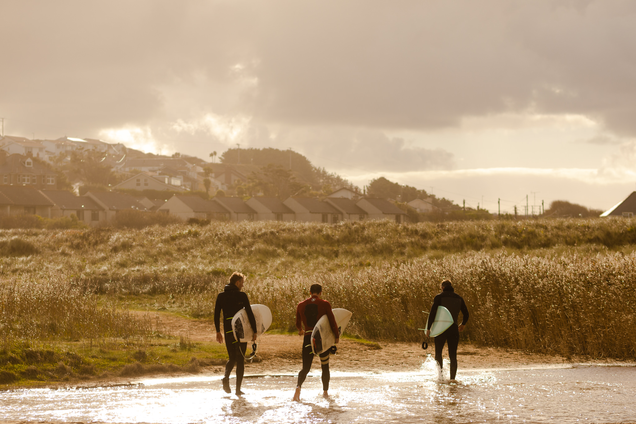 3 men carrying surfboards walking through the dunes at Holywell Bay