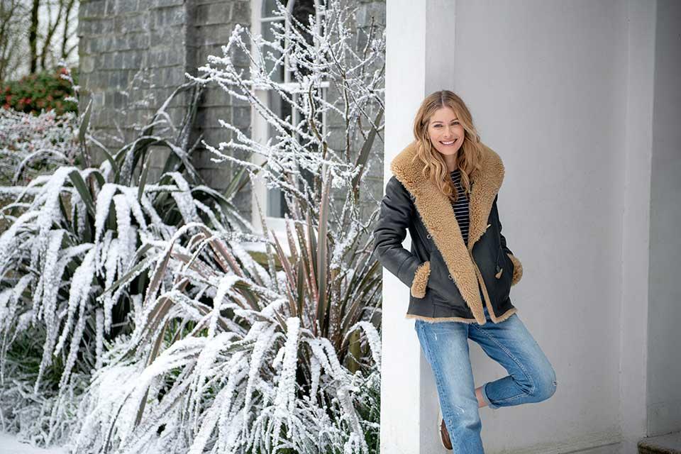 Celtic & Co photoshoot woman leaning on wall wearing sheepskin coat