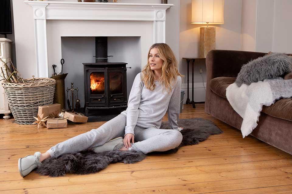 woman relaxing in front of roaring fire wearing cosy loungewear and sheepskin slippers