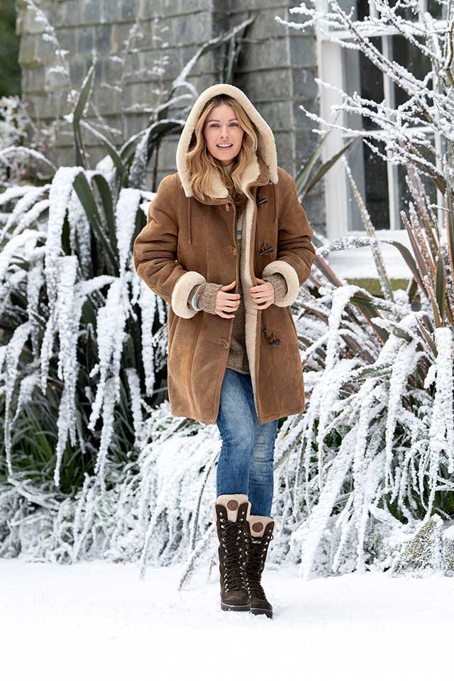 model wearing Celtic & Co sheepskin coat with hood up in the snow