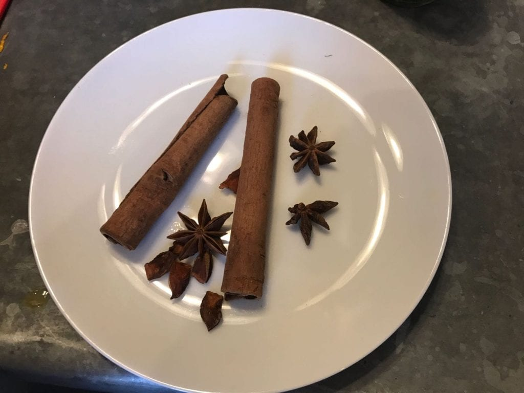 Cinnamon sticks and stare anise on white plate