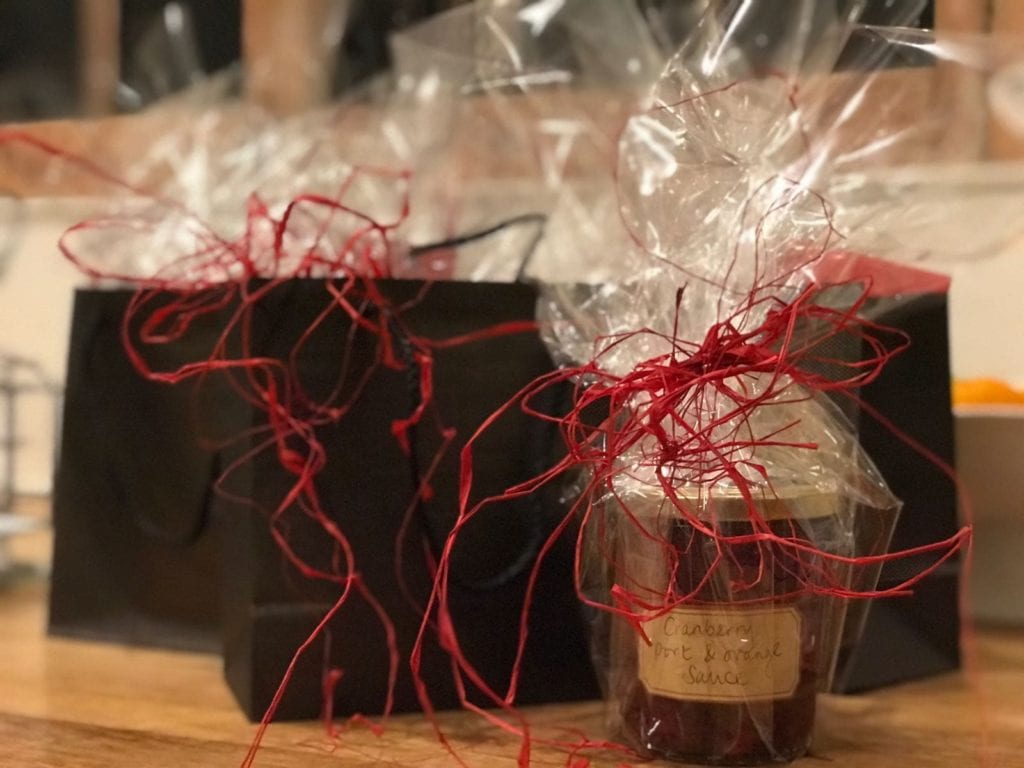 Homemade cranberry sauce in glass jar with red raffia and handwritten label