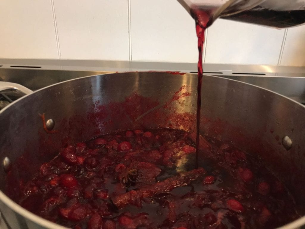Simmering cranberries and port in stainless steel pan