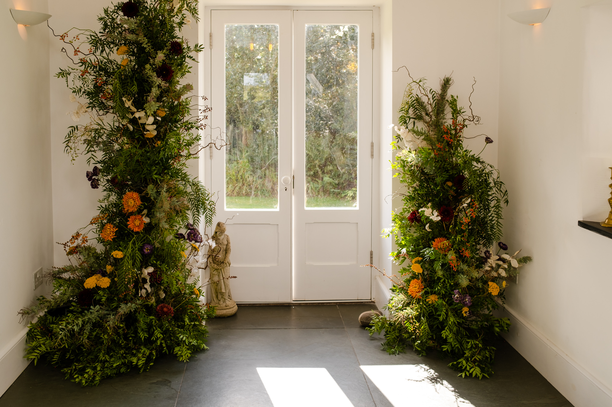 autumn wedding flowers installation over french doors