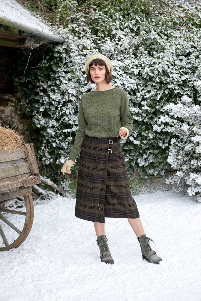 Model posting for winter photoshoot in the snow wearing plaid skirt