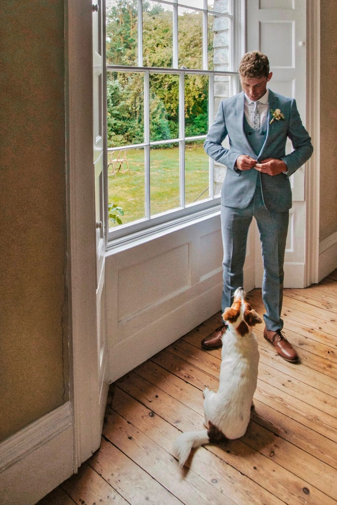 groom in suit in bay window with small dog at feet