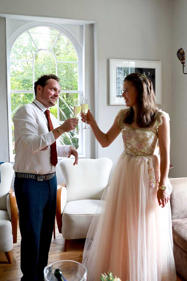 bride and groom celebrating with a glass of champagne