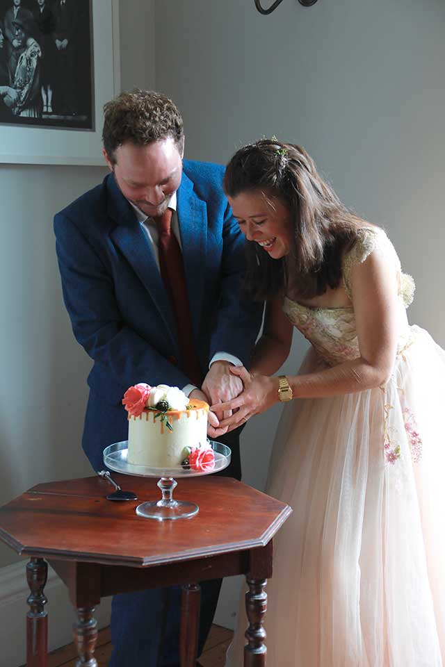 bride and groom cutting small wedding cake
