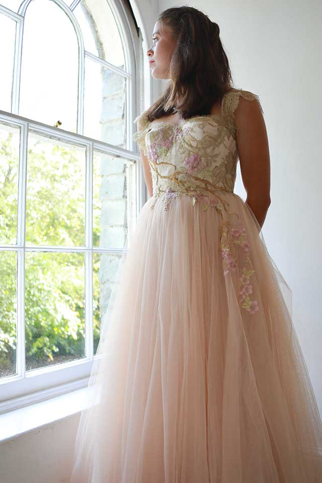 beautiful bride in pink fairytale wedding dress looking out of window