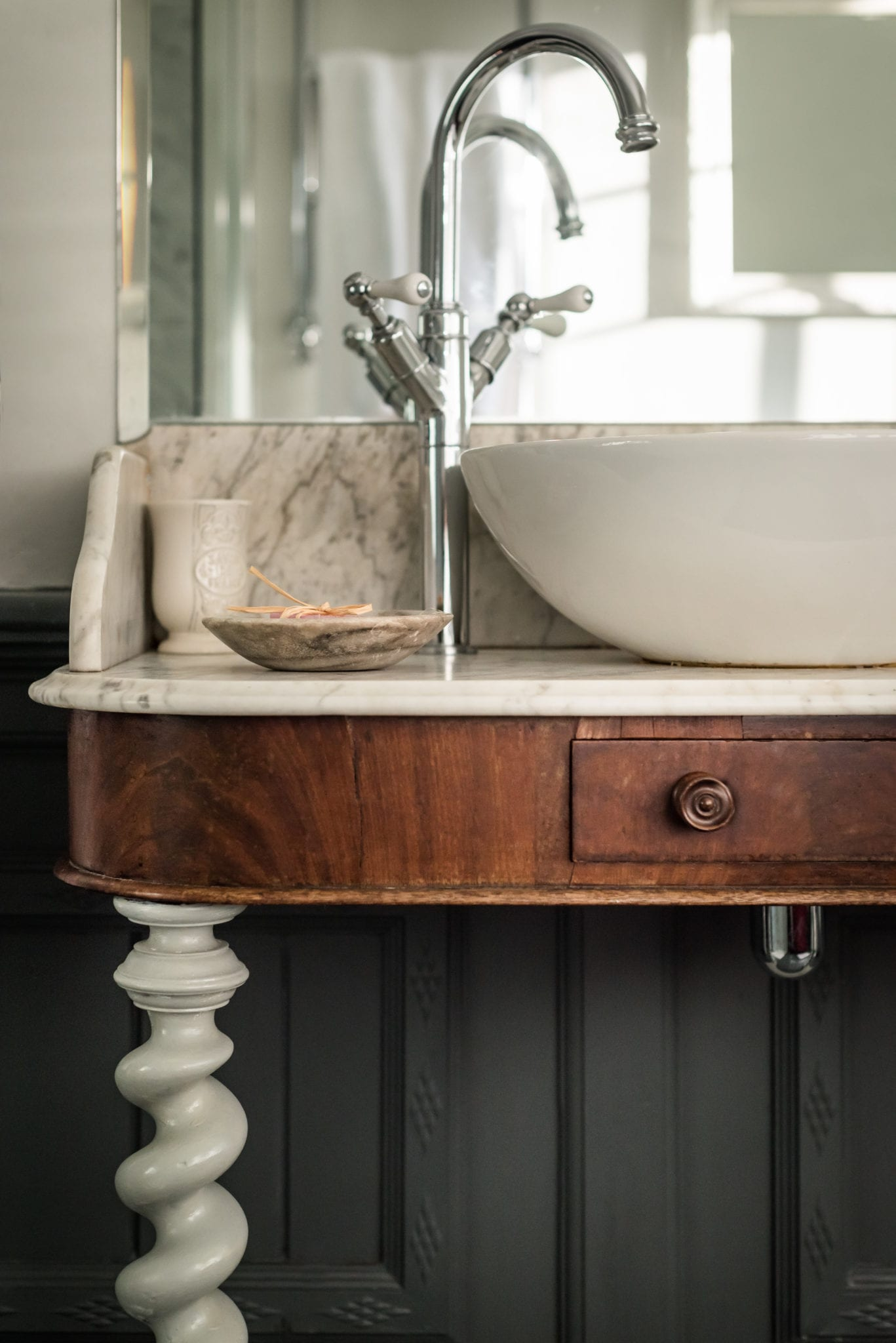 vintage washstand in bathroom with modern sink and marble top