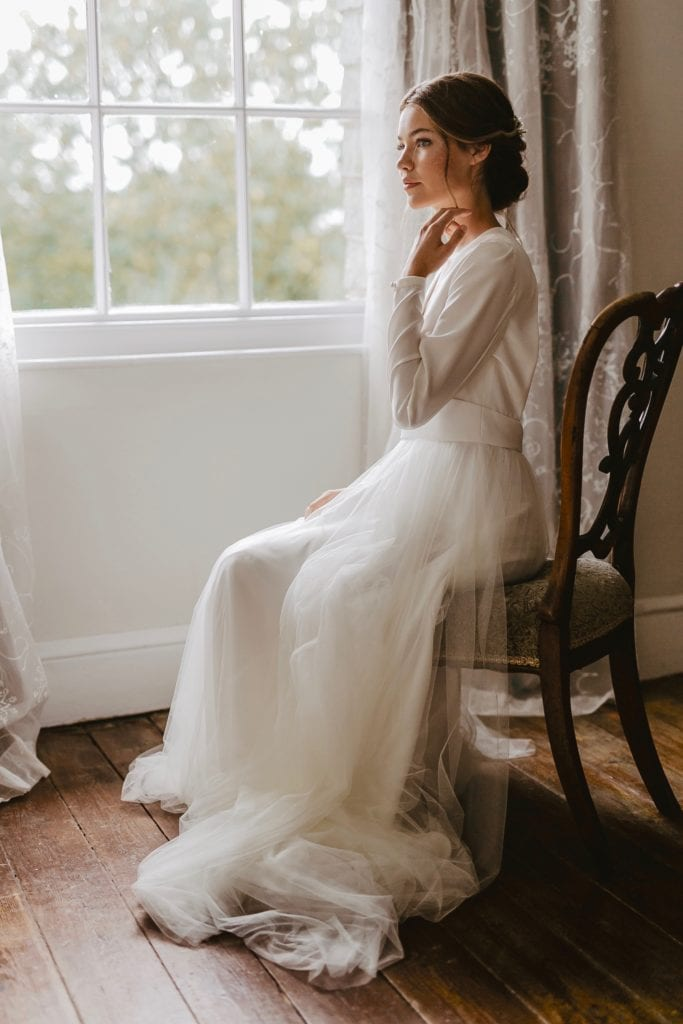 Bride in white wedding dress sat in Georgian bay window