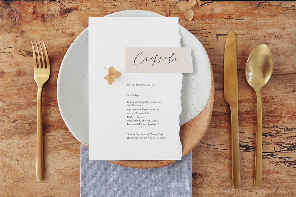 table setting with bespoke stationery and gold cutlery