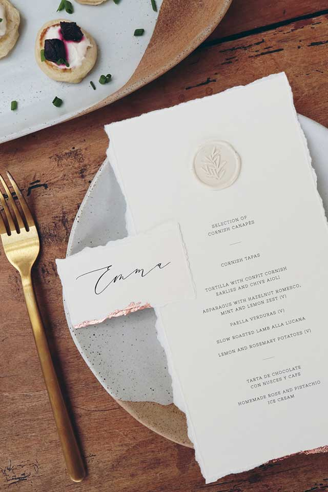Calligraphy handmade wedding menu on textured paper with copper cutlery