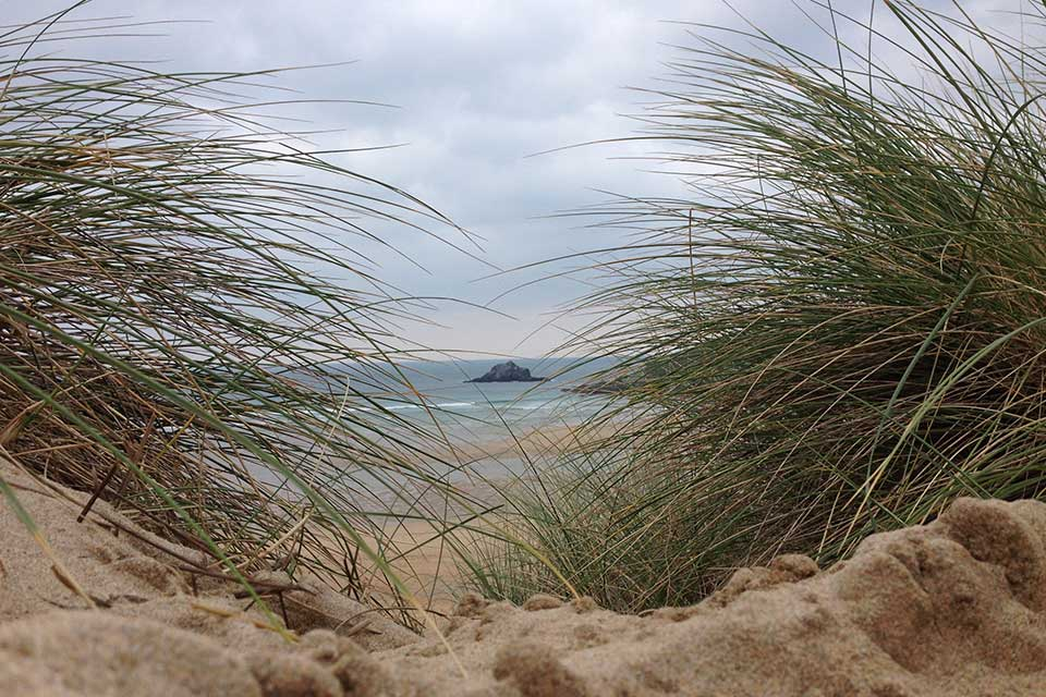 View of sea through sand dunes Holywell Bay Cornwall