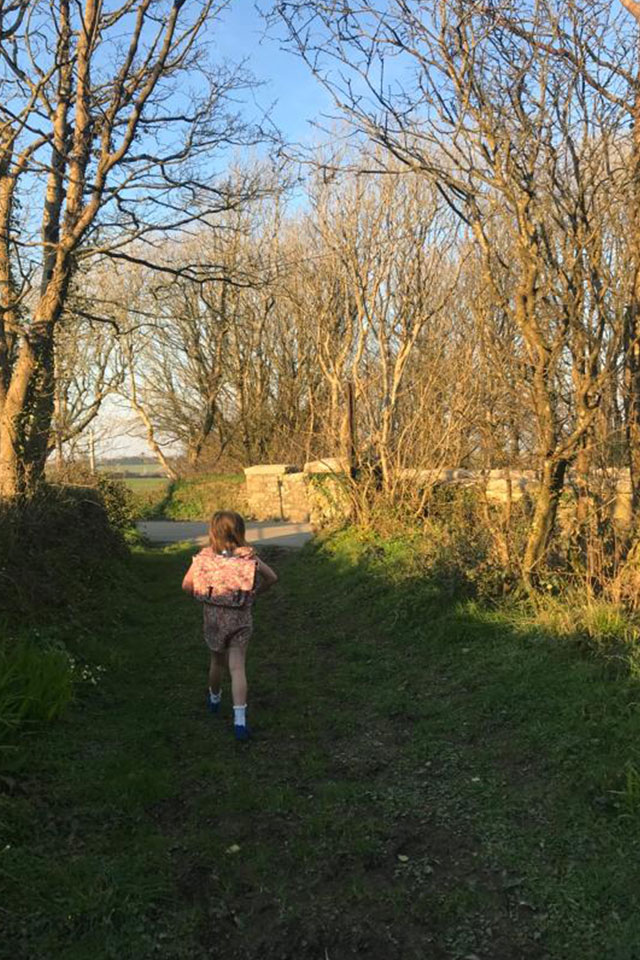 little girl with backpack on walk down Cornwall country lane