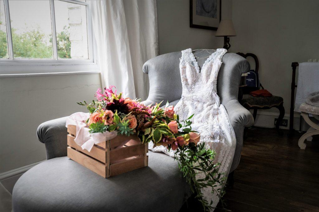 white lace wedding dress and colourful wedding flowers on grey chaise lounge