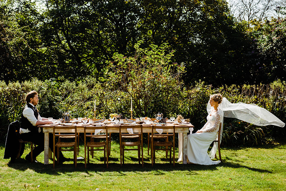 vintage wedding table setting in garden with bride and groom