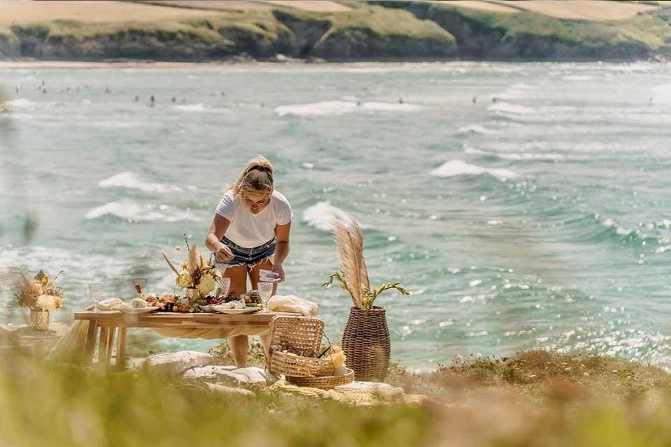 Dine with Iris setting up picnic on Cornish beach