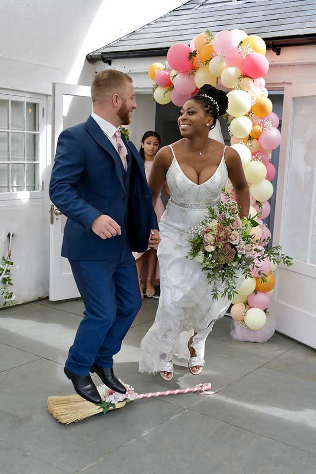 bride and groom jumping over the broom during small wedding ceremony