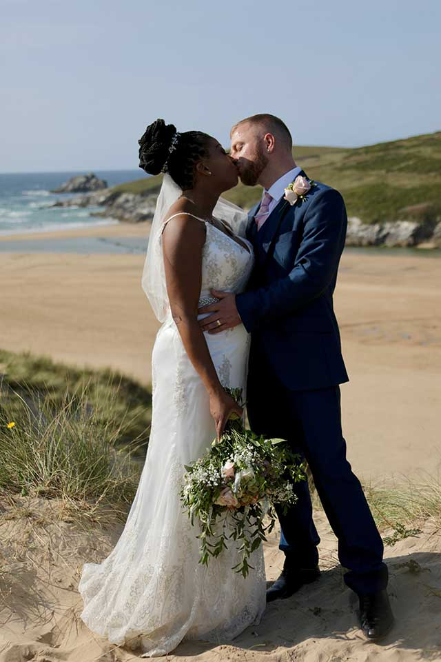 bride and groom kiss on the beach in Cornwall