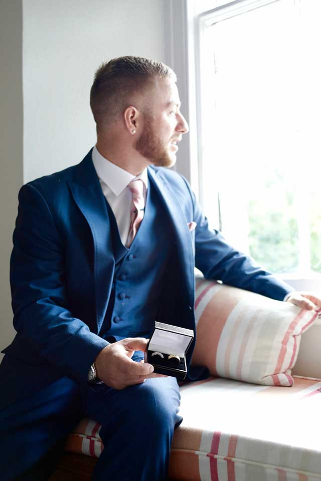 groom holding wedding rings looking out of window