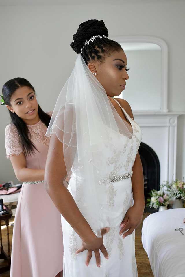 daughter helping her mum put on white wedding dress