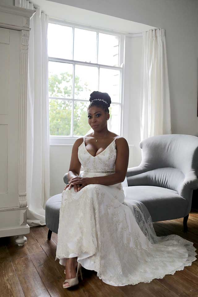 bride sat on chaise lounge wearing white lace wedding dress