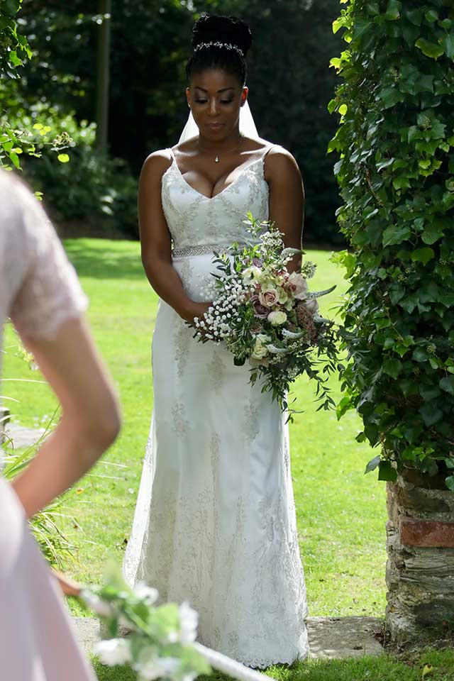 bride wearing white lace wedding dress holding blush pink flowers in green garden