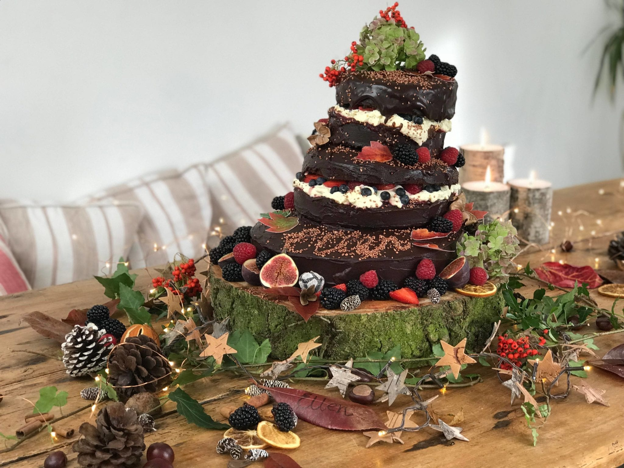 3 tiered chocolate birthday cake with fresh cream and fruit and autumnal table decorations