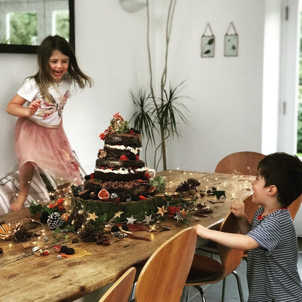 young boy and young girl playing around party table with birthday cake