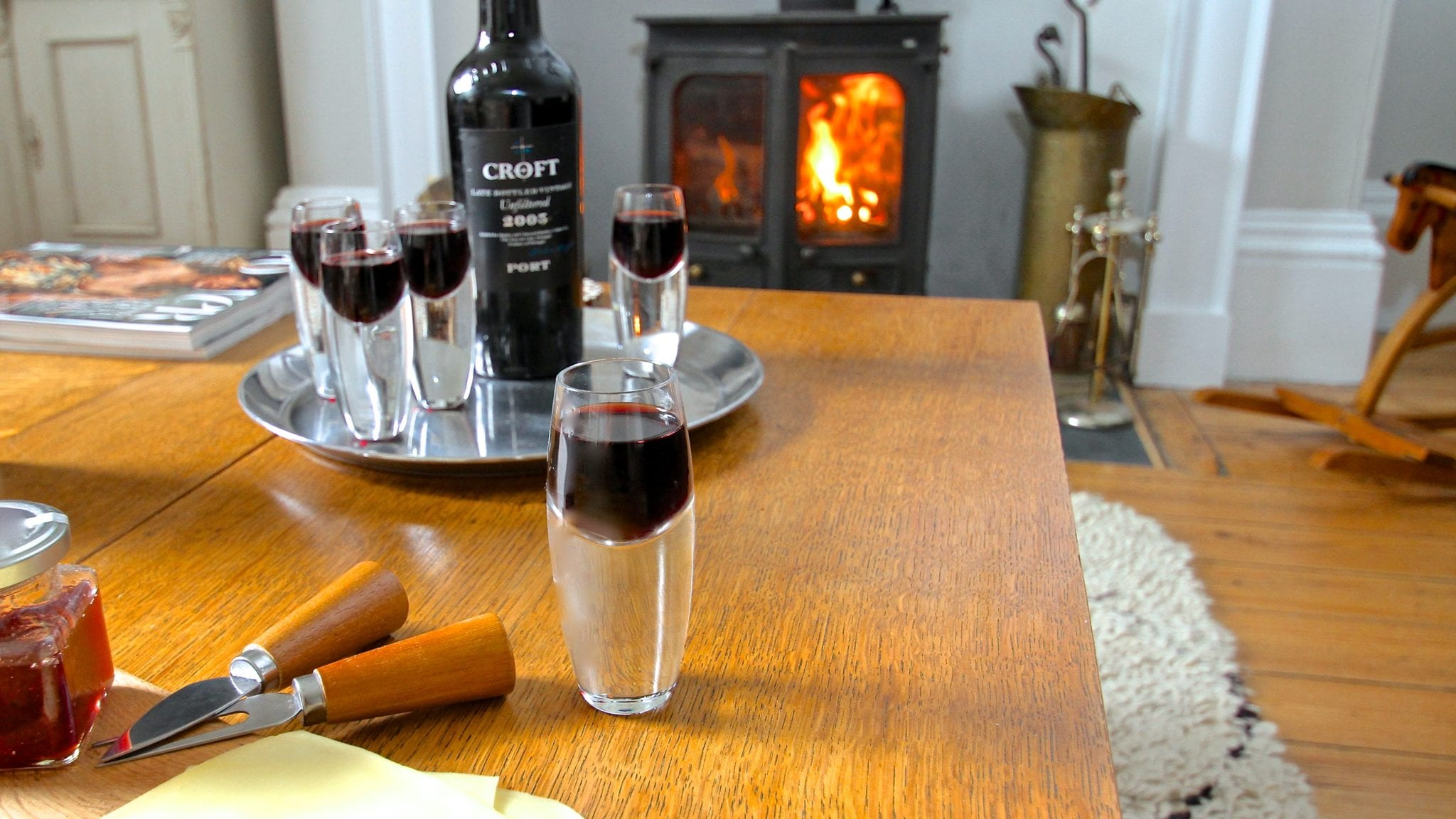 glasses of port and bottle on tray by roaring log fire