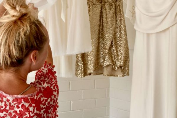 Bride's wedding dress and bridesmaids dresses hanging up with bride in red gown looking through them