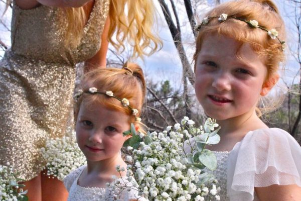 Bridesmaids in white dresses with gypsohilia bouquets and chief bridesmaid in gold sequinned dress