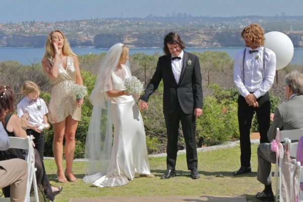 Bride and Groom holding hands with bridesmaid and best man looking on. View of Sydney Harbour