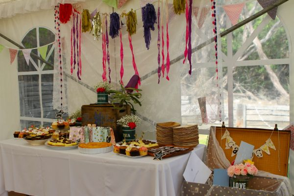 Wedding table set with food and pink and purple decorations with vintage trunk for cards