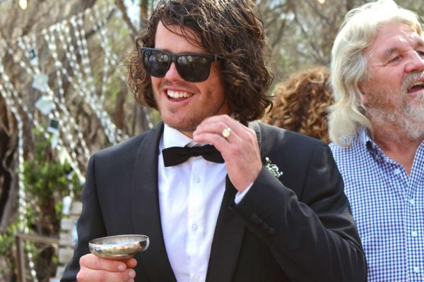 Groom with bow tie and champagne saucer at wedding