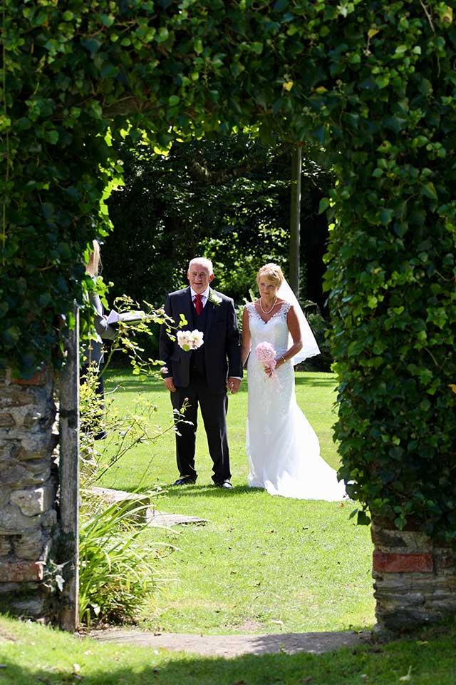 older wedding couple walking towards ceremony in bright sunshine