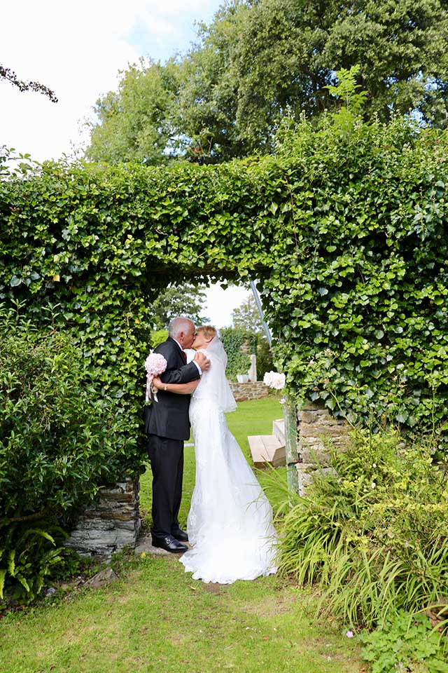 older wedding couple kissing under green ivy arch