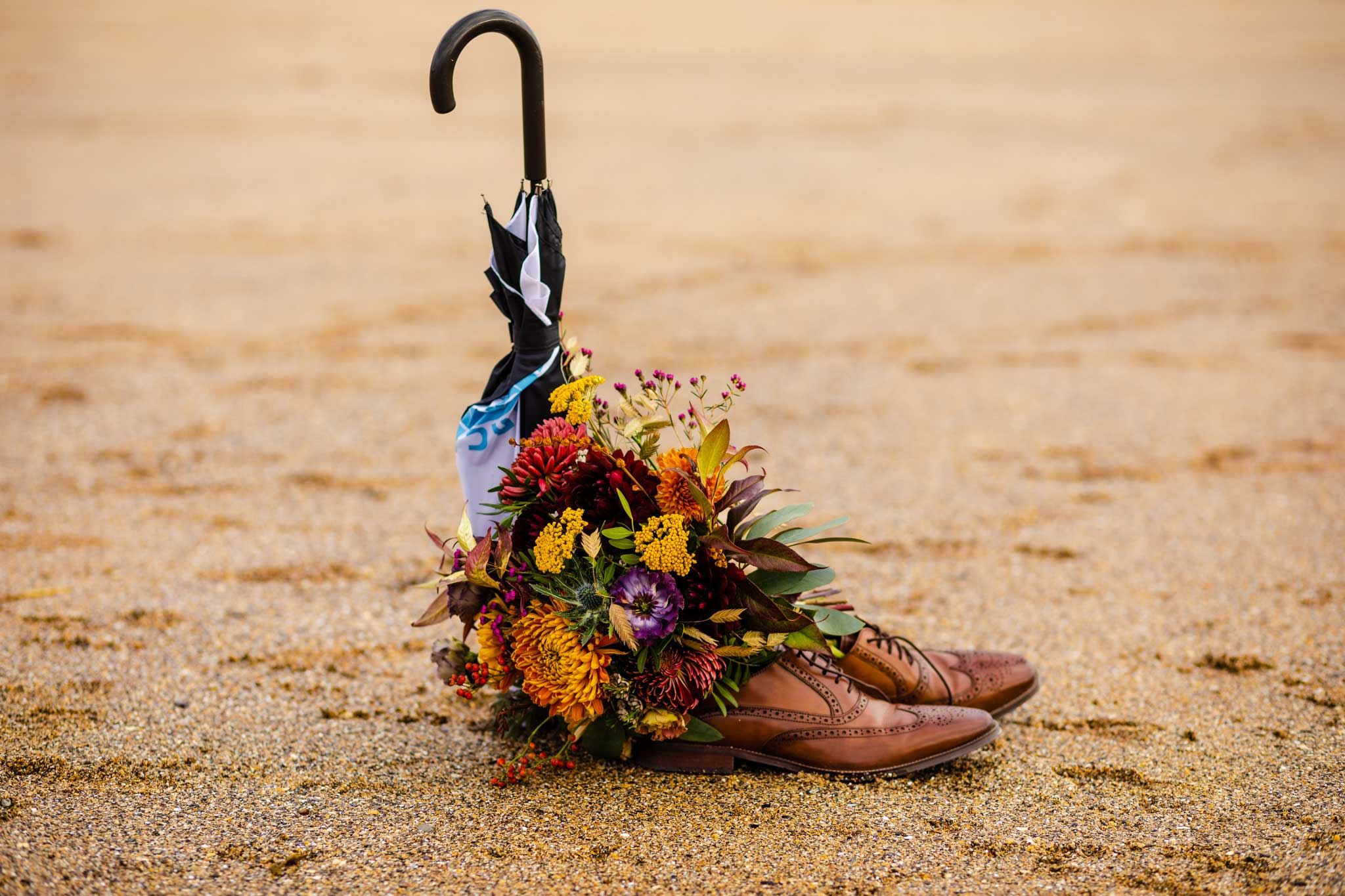 brown leather shoes with autumn wedding flowers and umbrella on beach