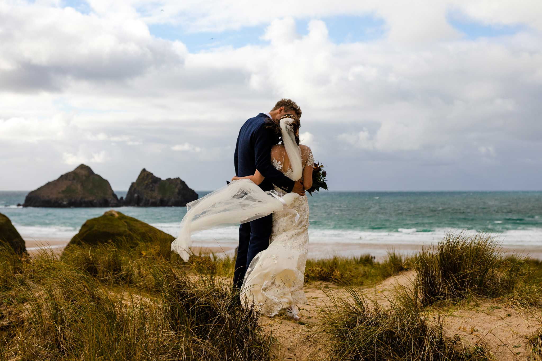 bride and groom embrace on the beach