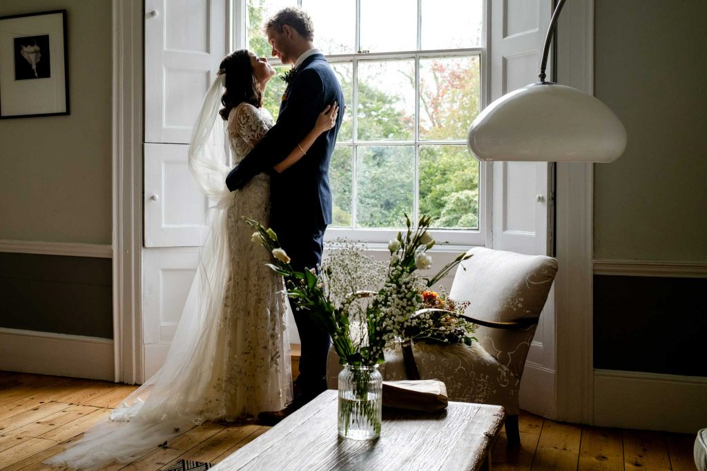 bride and groom smiling at each other in drawing room