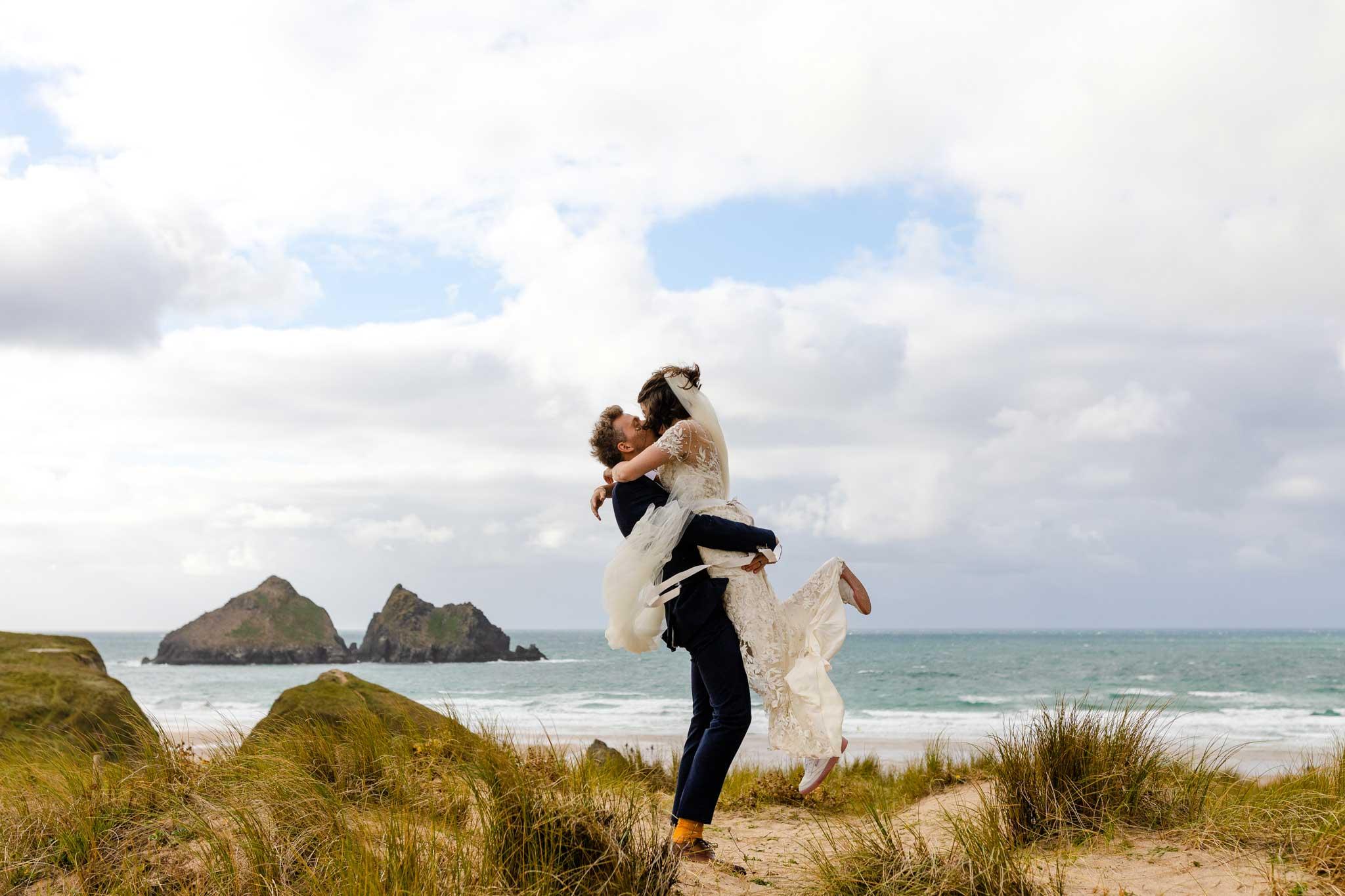 bride and groom embrace on Cornish beach