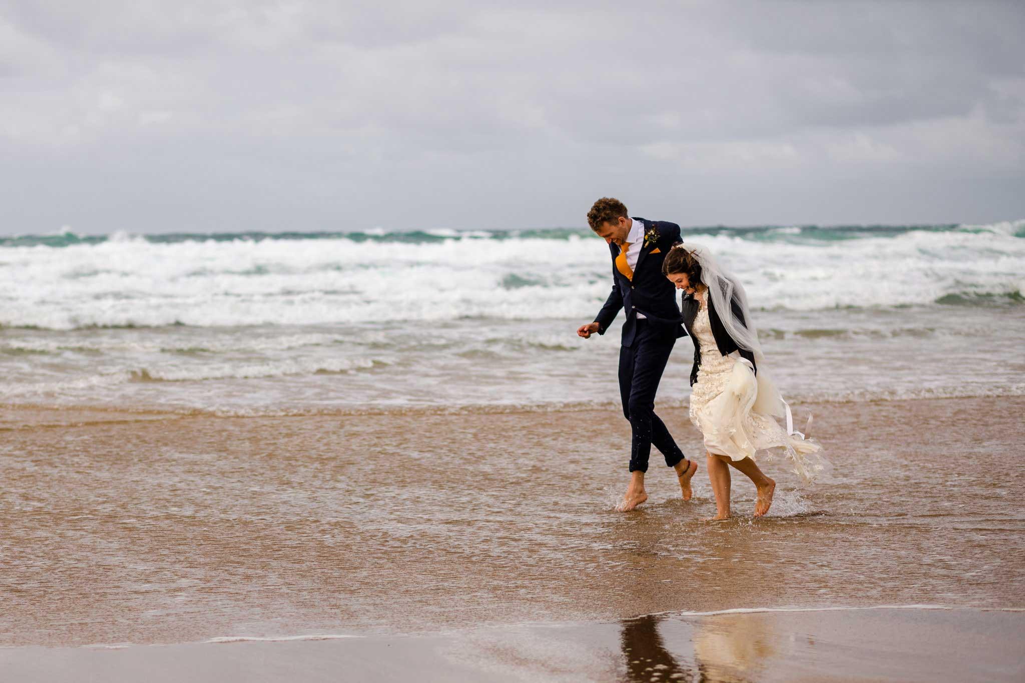 wedding couple walking in the sea