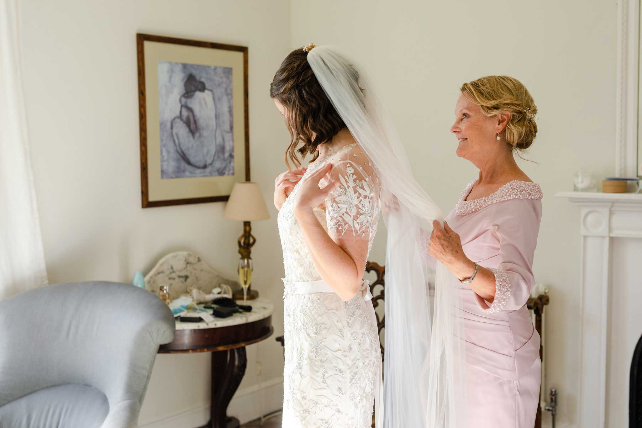 mother helping daughter into wedding dress