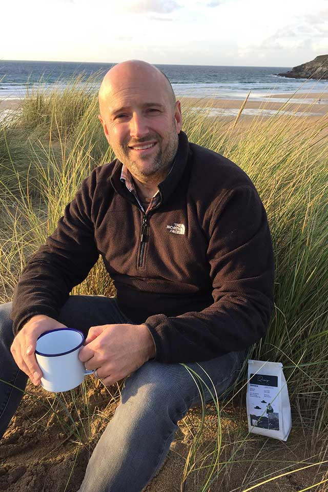 Andrew from Quay Coffee on the beach with a coffee in white enamel mug