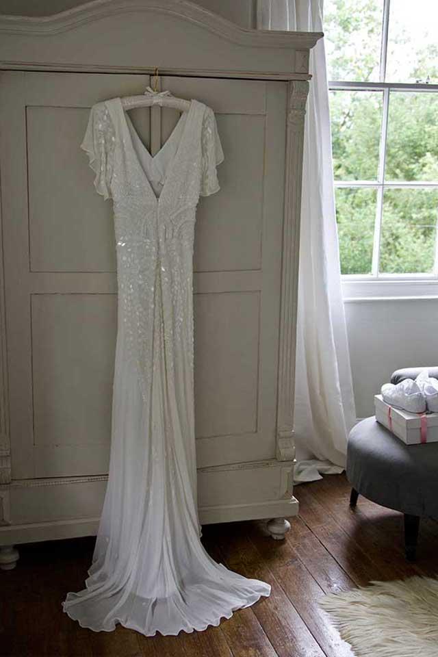 sequing wedding dress hanging on wardrobe