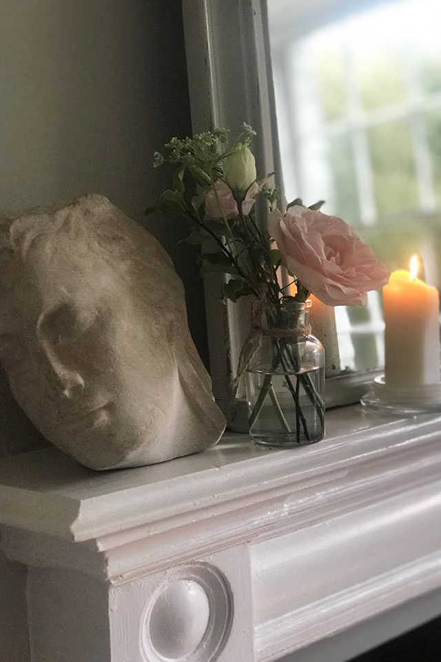 small face stone carving on mantlepiece