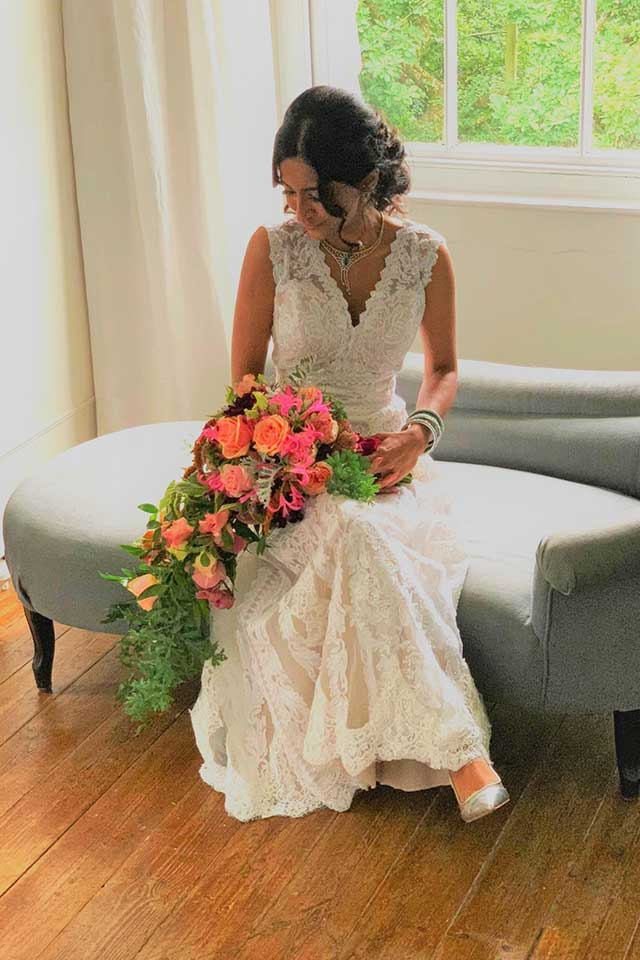bride sat in bridal suite in wedding dress with bouquet