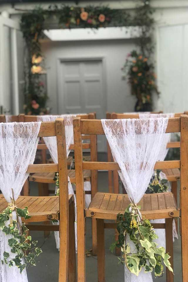 wooden chairs with lace chair backs set up for small wedding ceremony